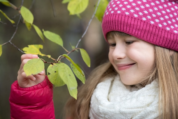 Pretty child girl wearing warm winter clothes holding tree branch with green leaves in cold weather outdoors.