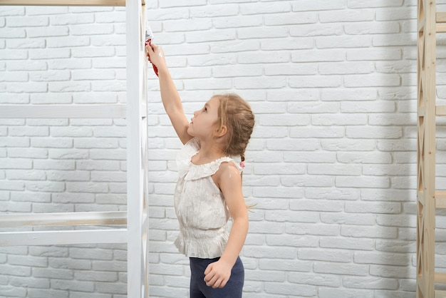 Pretty child painting with brush and white color wooden rack