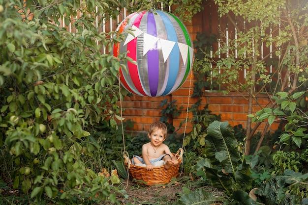 Симпатичный ребенок верхом на воздушном шаре мальчик весело взлетает