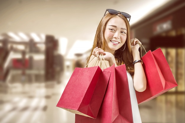 Pretty chinese woman carrying shopping bags at mall