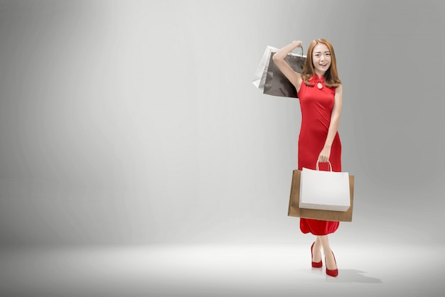 Pretty chinese woman with cheongsam dress carrying shopping bags