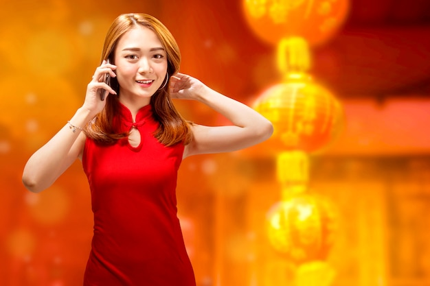 Pretty chinese woman with cheongsam dress talking on the phone