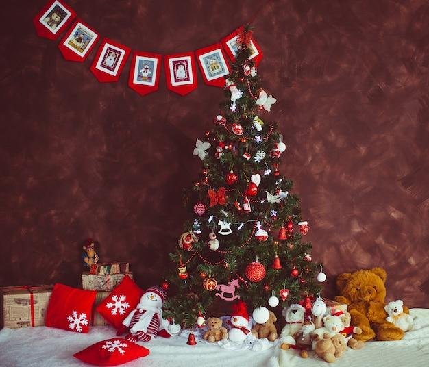 예쁜 크리스마스 트리 빨간 벽 앞에 서