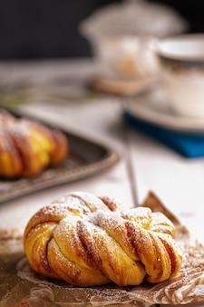 白い木製のテーブルにかわいいシナモンの結び目のパン