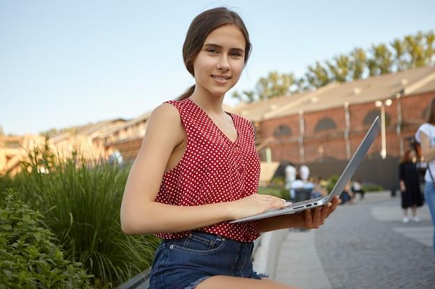ポータブルコンピュータを使用してキャンパスのベンチに座って、歴史に関するレポートを準備しているスタイリッシュな夏服を着たかわいい大学生の女の子。屋外のラップトップでインターネットサーフィン美しい若い女性