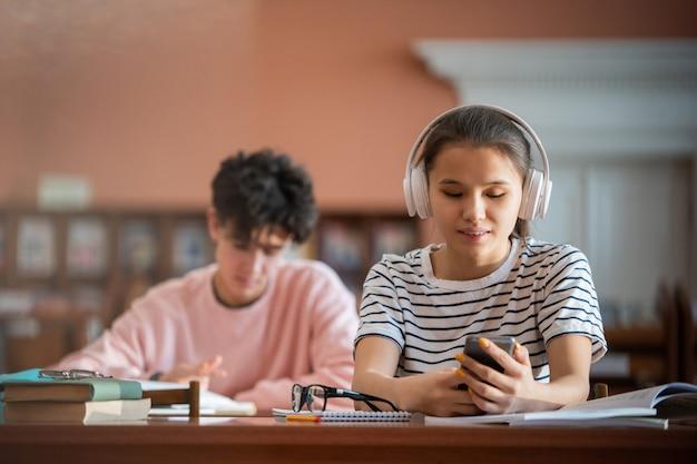Симпатичная студентка колледжа с наушниками прокручивает смартфон, сидя за столом в читальном зале библиотеки колледжа