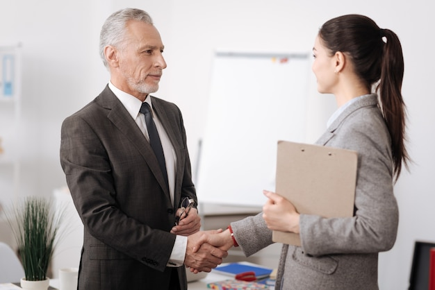 Pretty competent female holding folder with documents shaking hands with her boss