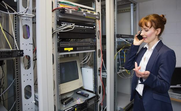 Довольно компьютерный техник, разговаривающий по телефону рядом с открытым сервером