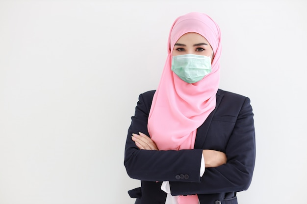 Pretty and confident muslim young asian woman wearing blue suit with medical protective face mask to protect infection from coronavirus in studio on isolated white background portrait