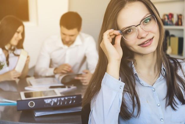 話をしている同僚と背景に笑みを浮かべて眼鏡をかけたかなり自信のあるオフィスの女性。教師の女性はクラスでクローズアップ