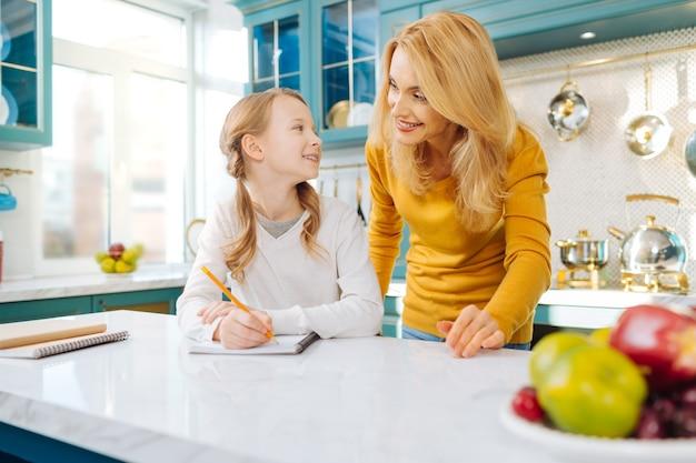 Довольно довольная белокурая девушка улыбается и держит карандаш, глядя на свою мать, стоящую за ее спиной
