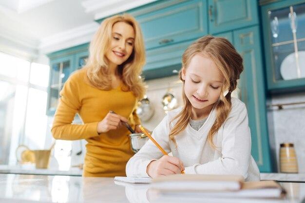 Довольно довольная светловолосая девушка улыбается и пишет в блокноте, в то время как ее мать стоит позади нее с кастрюлькой