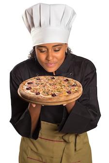 白いスペースにハムピザの匂いを嗅ぐかわいい料理人の女性