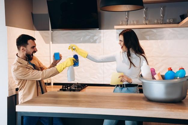 キッチンで掃除道具を使って楽しく、喧嘩するふりをするかわいいカップル