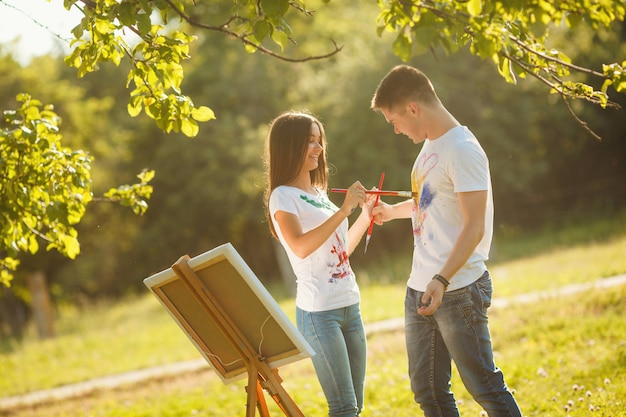 Pretty couple having fun at open air outdoors. young man and woman drawing by colorful paints on each other`s t-shirts with brushes near the easel on the nature.