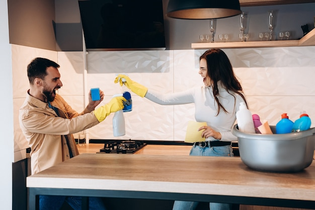 Pretty couple having fun and pretending fight with cleaning tools in kitchen