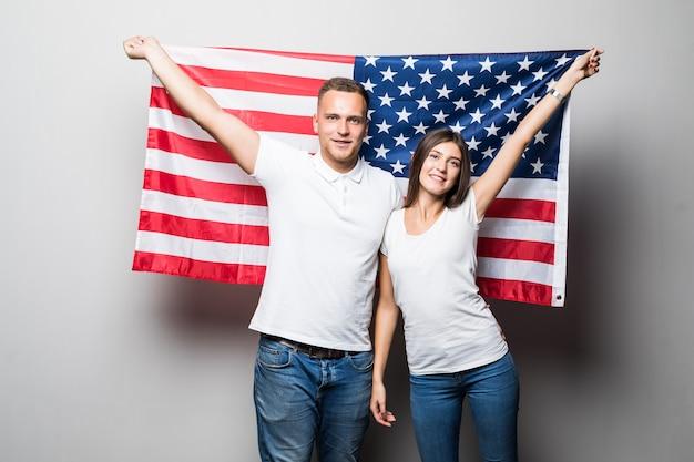 La coppia graziosa tiene la bandiera degli stati uniti nelle loro mani, si coprono isolato su bianco