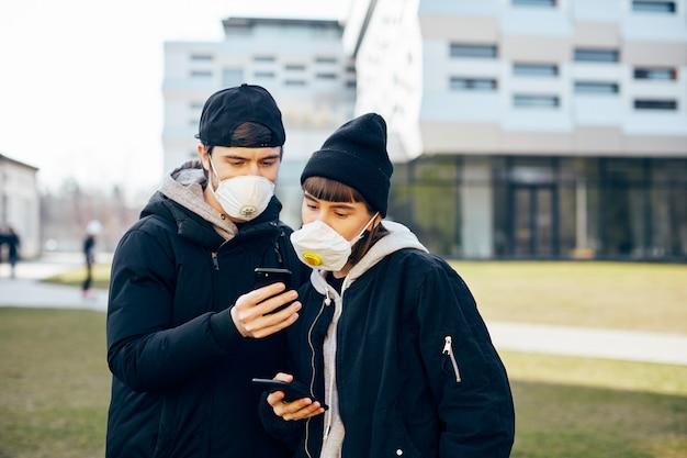 호흡 마스크에 현대 건축과 거리에 서서 전화 뉴스를 보여주는 검은 옷을 입은 예쁜 커플, 세련된 남자가 마스크에 야외 소녀에게 새로운 telepnone을 보여주는 세련된 남자