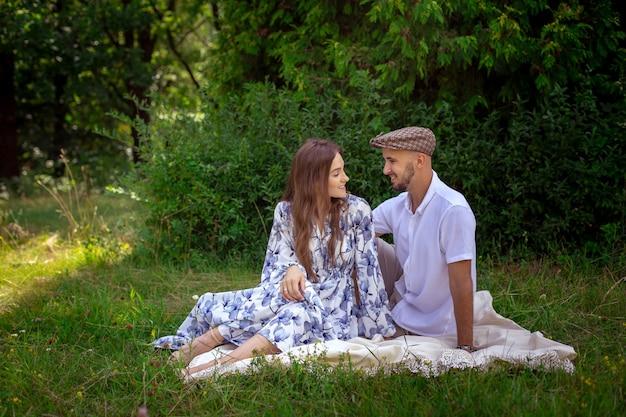 피크닉에서 사랑에 예쁜 부부는 녹색 자연에서 서로 미소 짓는다.