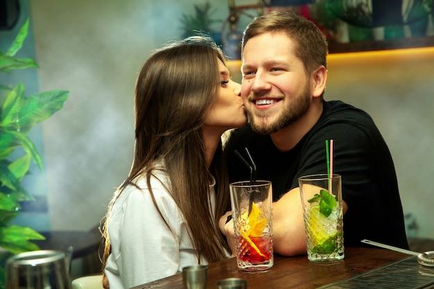 알코올 칵테일 바에서 재미 사랑에 예쁜 커플. 소녀는 그녀의 남자 친구를 키스