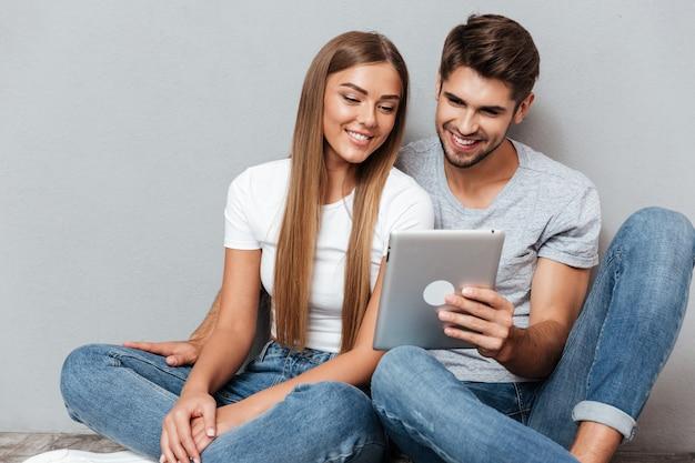 Красивая пара, глядя в планшет