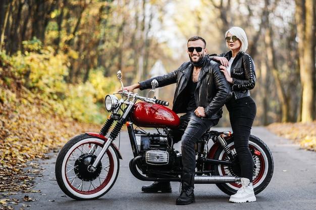 Красивая пара возле красного мотоцикла на дороге в лесу