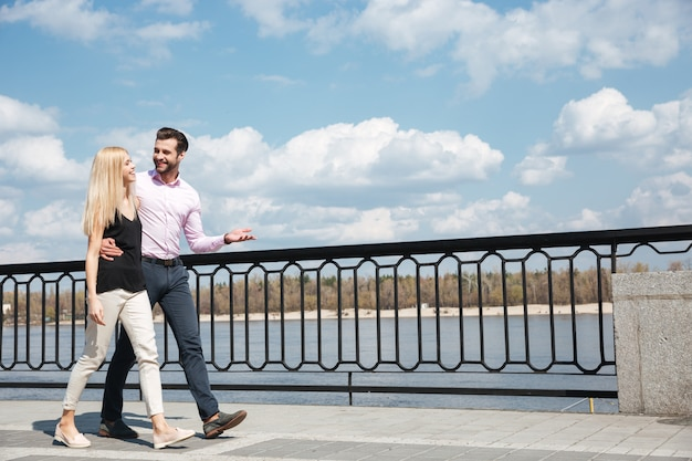 陽気な男性と女性が通りを歩いてのかなりのカップル