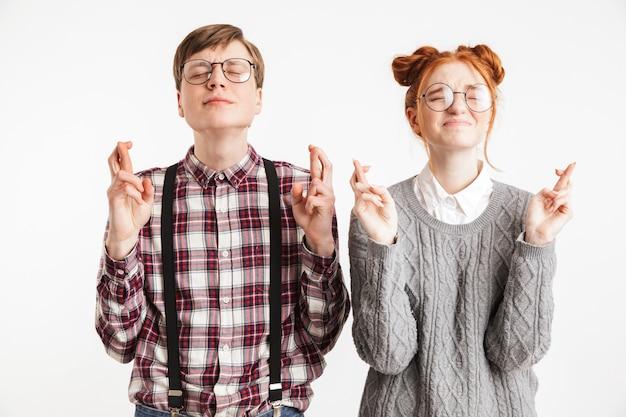 交差した指を保持している学校のオタクのかなりのカップル