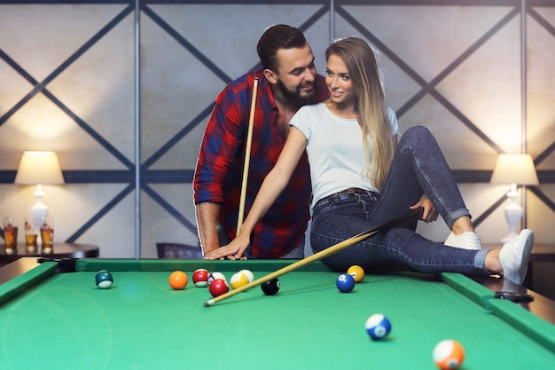 Красивая пара играет в бильярд