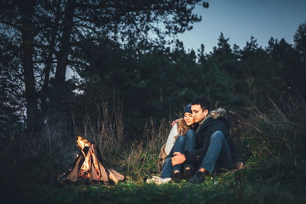 Pretty couple relaxing near bonfire in the forest at evening time