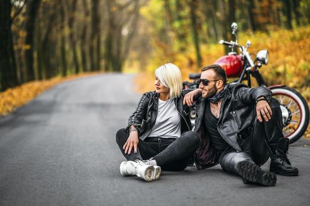 森の道で赤いバイクの近くに座っているかわいいカップル