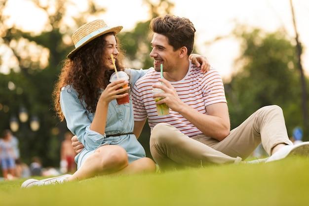 Красивая пара сидит на зеленой траве в парке и пьет напитки из пластиковых стаканчиков