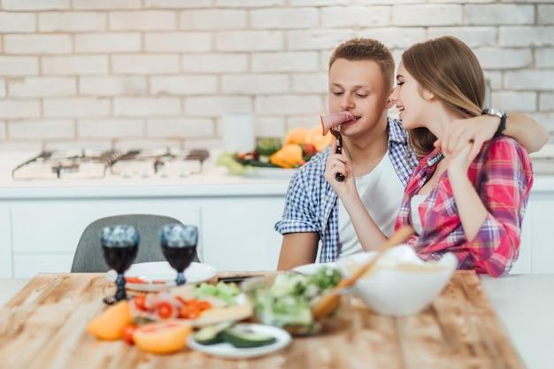 家庭の台所でハムを乾杯するかわいいカップル。