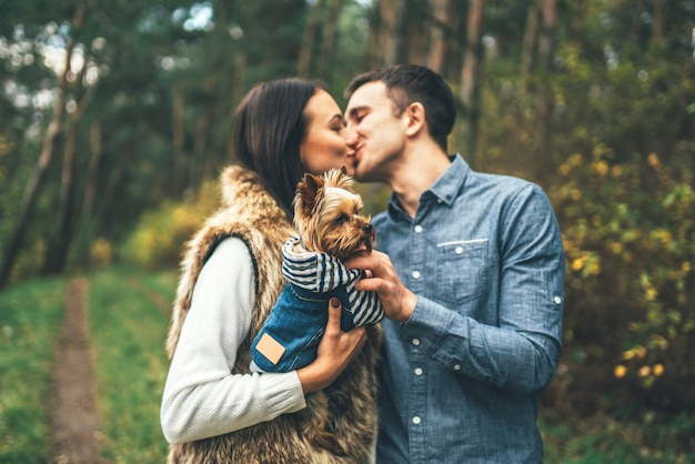 Pretty couple with little yorkshire terrier walking in the forest.