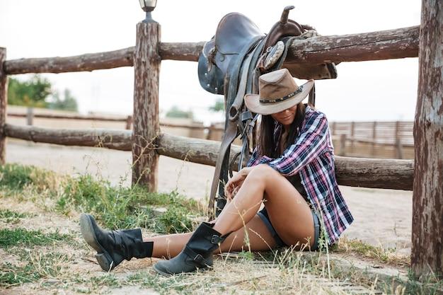 牧場の柵に寄りかかって休んでいる帽子のかわいい騎乗位