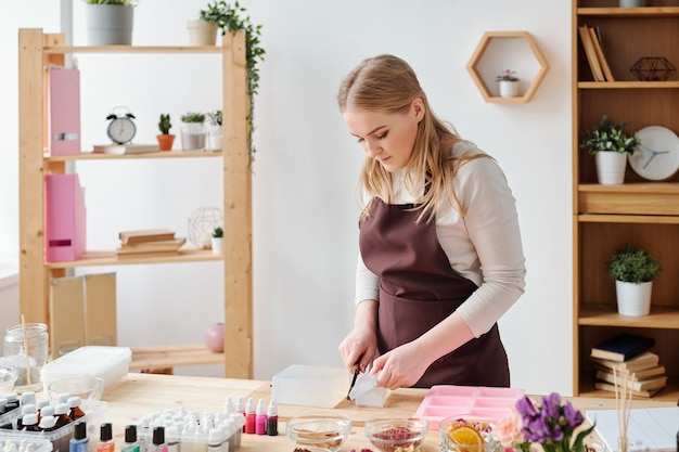 Красивая мастерица в коричневом фартуке режет большой кусок твердой мыльной массы перед дальнейшей обработкой во время работы в студии