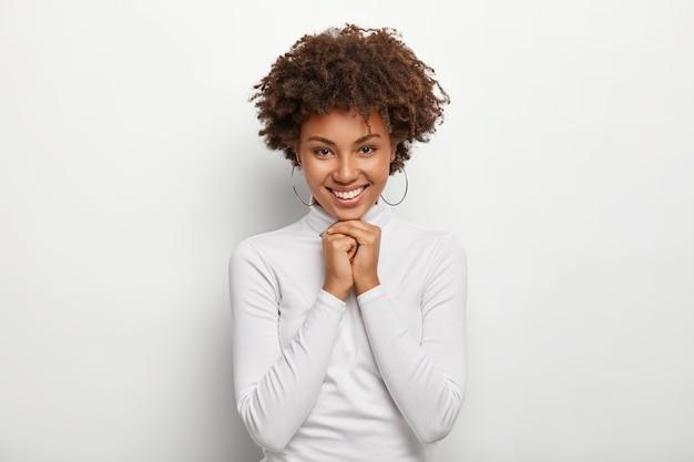 Ragazza graziosa con capelli afro, tiene le mani unite sotto il mento, ha un'espressione felice, indossa orecchini rotondi, maglione a collo alto