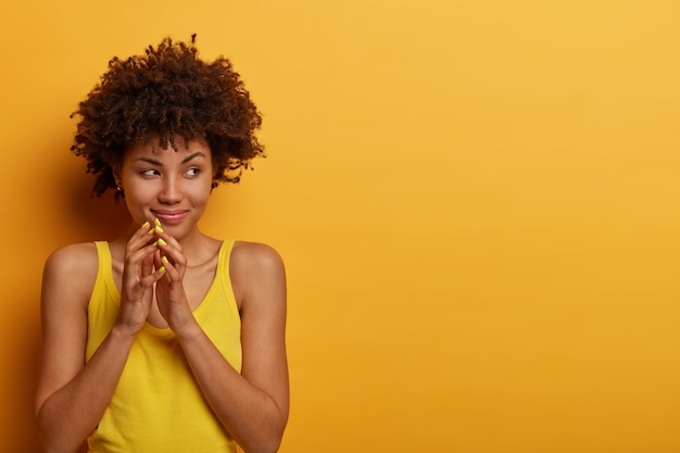 Pretty cunning woman steepls fingers, looks mysteriously aside, has evil plan, wants to prepare surprise for husband, wears casual shirt, isolated on yellow wall, copy space area