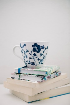Pretty cup on pile of books