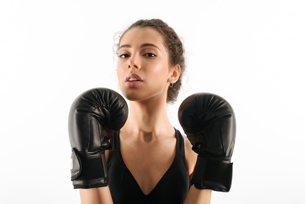Pretty curly brunette fitness woman in boxing gloves