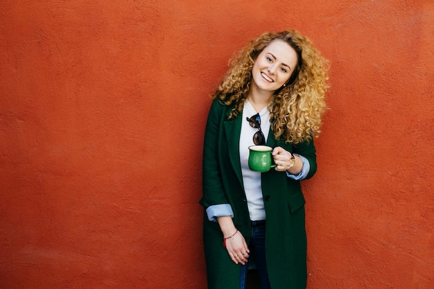 Pretty curly female wearing stylish clothes holding cup of coffee having broad smile on face.