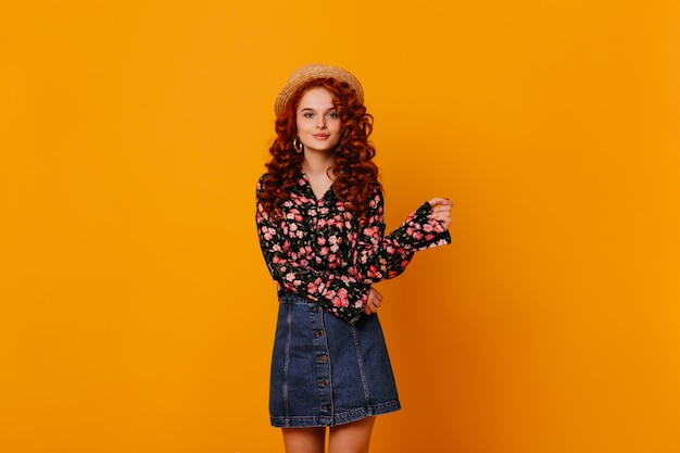 Pretty curly girl in boater, bright blouse and blue skirt moves on isolated orange space.