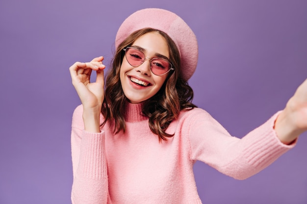 ピンクのセーターとベレー帽のかわいい巻き毛の女の子が自分撮りを取ります
