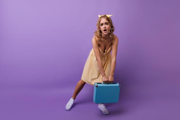 重いスーツケースでポーズをとるかわいい巻き毛の女の子。バイオレットにスーツケースを持っているデボネアのヨーロッパの女性。
