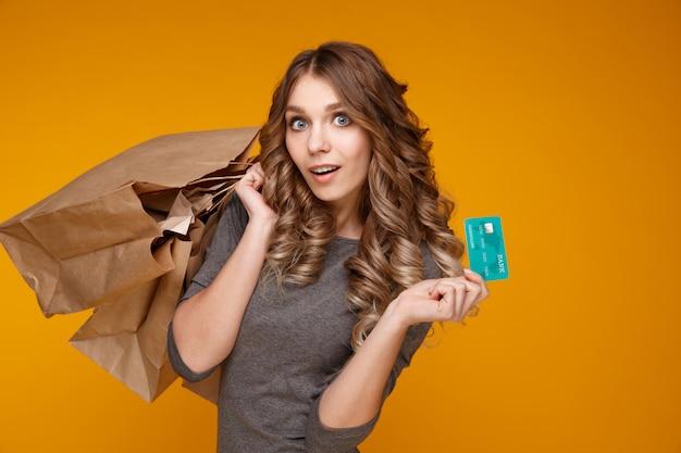 Модель довольно вьющиеся волосы позирует с сумками и кредитной картой