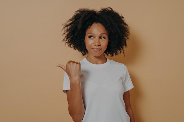 Симпатичная кудрявая африканка показывает пальцем в сторону, с радостью рекомендует промо и рекламирует товар, предлагает посетить это место, позируя на бежевом фоне.