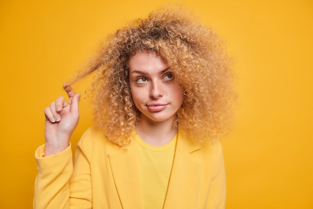 Pretty curly haired european woman curls hair looks away with pensive expression dressed in formal clothes considers something in mind isolated over vivid yellow wall. monochrome shot.