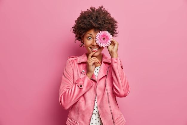 Bella signora dai capelli ricci con un sorriso a trentadue denti tiene il fiore rosa della gerbera davanti agli occhi, fiori raccolti dai prati primaverili in fiore, vestito con una giacca rosa, andando a fare una ghirlanda