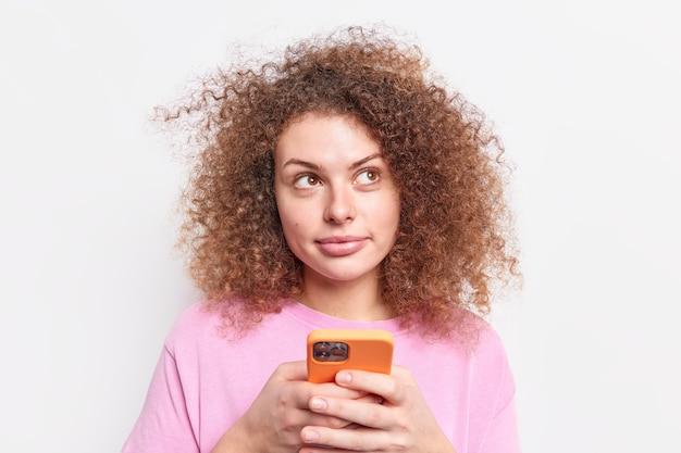 Симпатичная кудрявая девочка-подросток использует современный смартфон, задумчиво смотрит где-то, проверяет ленту новостей, подключенную к беспроводному интернету, одетая небрежно изолированно на белой стене, набирает смс