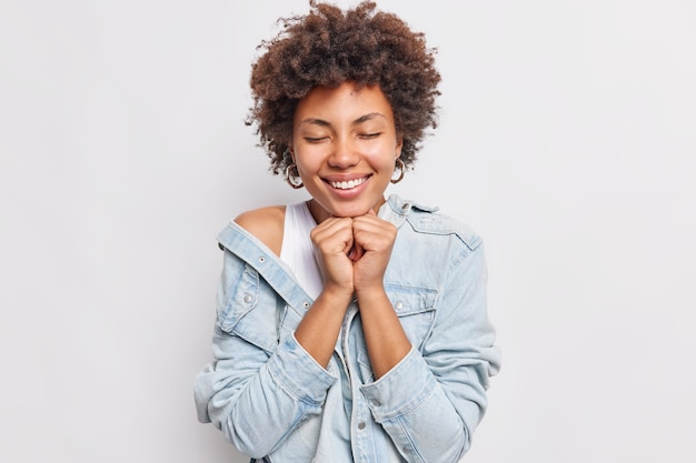 예쁜 곱슬머리 여성이 눈을 감고 활짝 웃고 턱 아래에 손을 얹고 부드러운 표정을 지으며 흰 벽에 격리된 데님 재킷을 입는다